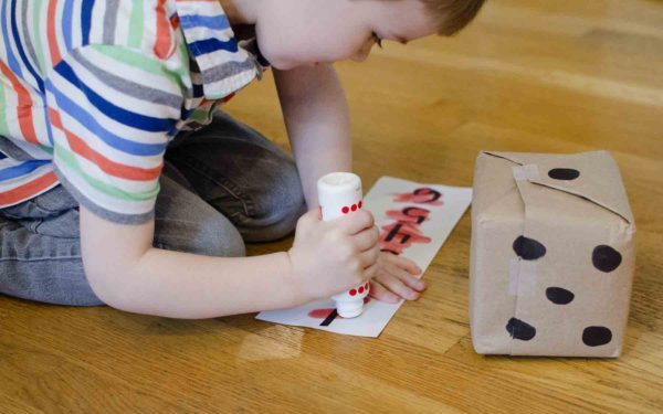 boy crossing out numbers during the roll and cross dice game