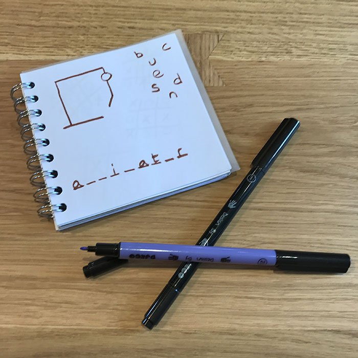 two pens and a paper with Hangman