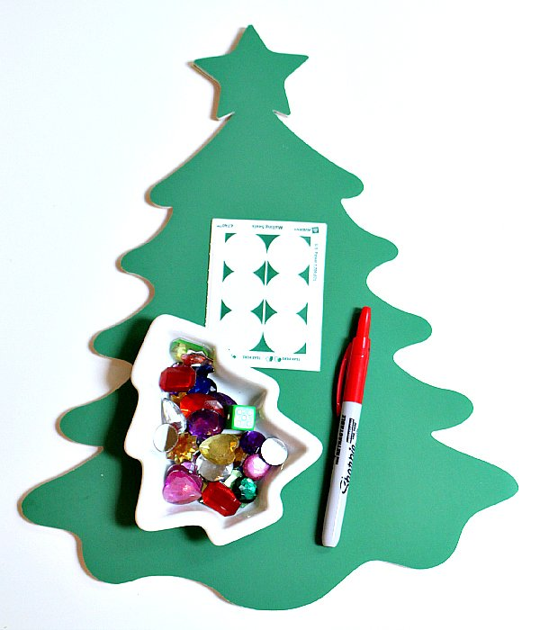 Christmas tree paper cutout, a marker, and beads