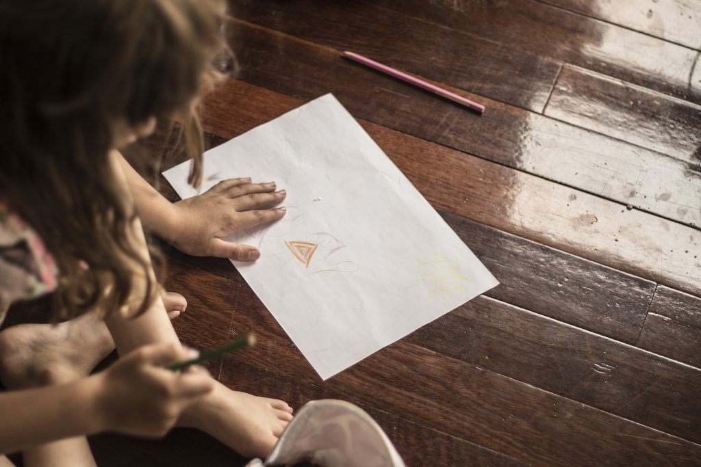 a kid doodling on a paper