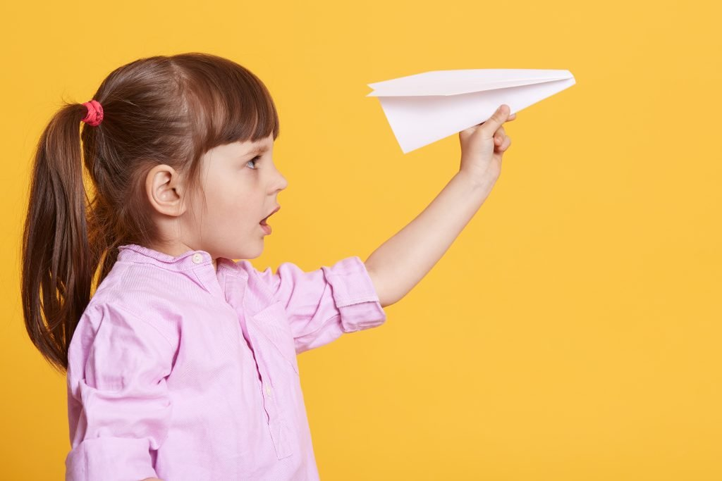 Side view of little cute female kid posing with white paper plane in hands, charming concentrated girl wearing rose shirt, having dark hair, female child being fond of origami. Childhood concept.