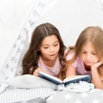Girls best friends read fairy tale before sleep. Best books for kids. Children read book in bed. Reading before bed can help sleep better at night. Stories every kid should read. Family tradition