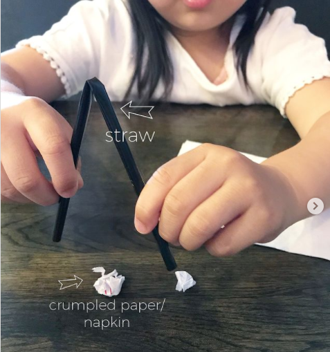kid picking up crumpled paper using a straw